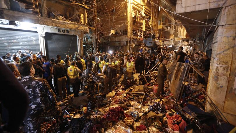 epaselect epa05022517 Lebanese policemen and citizens inspect the site where two suicide bombers blow themselves up in Bourj al-Barajneh, southern Beirut, Lebanon, 12 November 2015. At least 37 people were reported killed in a twin bombing that rocked a Hezbollah-stronghold in Beirut's southern suburbs.  EPA/NABIL MOUNZER